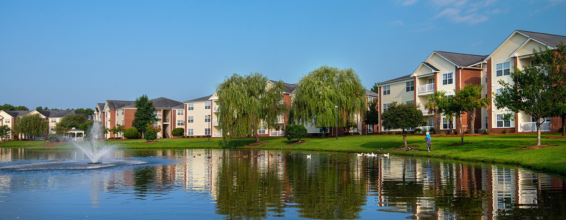 Seaside Grove apartments overlooking a pond with a fountain